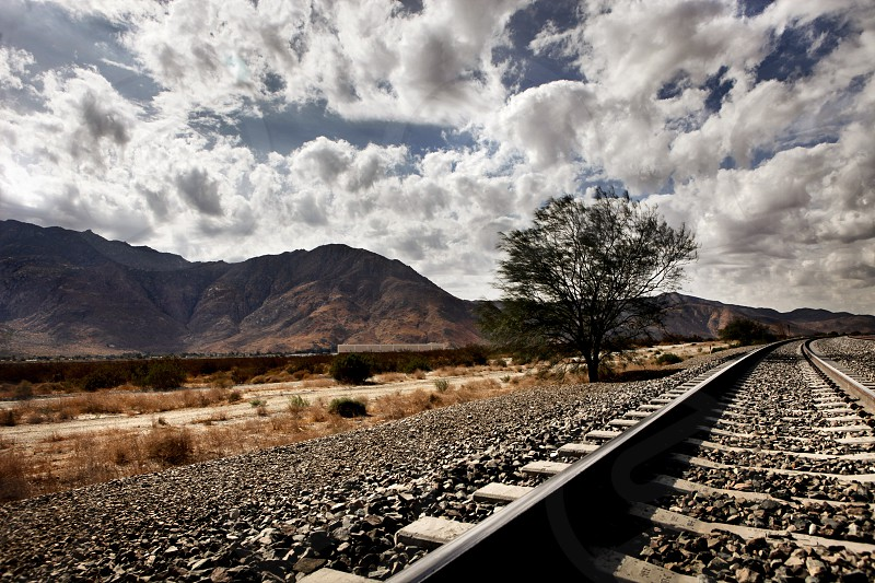 White fluffy distressed clouds over a harsh brown and grey landscape with rocks/pebbles/gravel weeds dirt mountains a railroad track and agree. photo