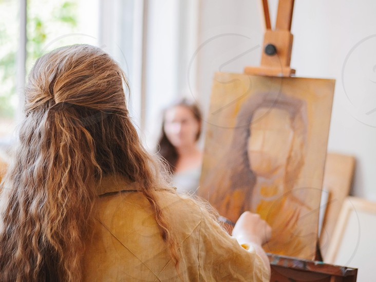 Girl is painting portrait of young woman in own studio. View from her back. Unrecognizable person with beautiful hair. photo