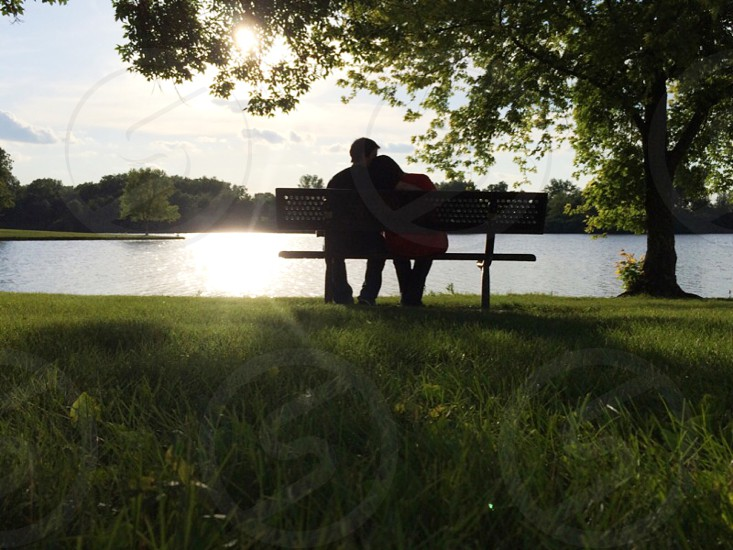 Love is when two people sit in the middle of the bench even where there is enough room on both ends.  photo