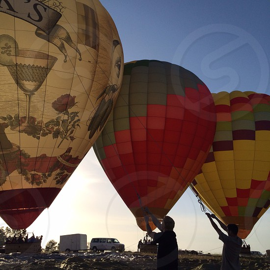 hot air balloons on hill top under blue sky photo