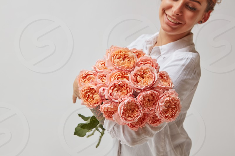 happy smiling girl holding a large bouquet of pink roses. valentine's day mother's day photo