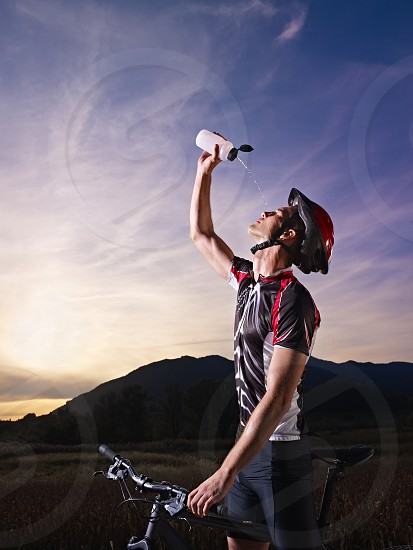 riding; bicycle; bike; biker; biking; man; mountain; 20s; active; activity; adult; adventure; beverage; caucasian; copy; space; country; cycle; cycling; cyclist; drink; drinking; dropping; energy; exercising; face; field; fitness; helmet; leisure; male; nature; one; outdoors; people; person; pouring; refreshing; refreshment; sky; spilling; sport; sportswear; summer; sun; sunset; sweat; training; water; young photo