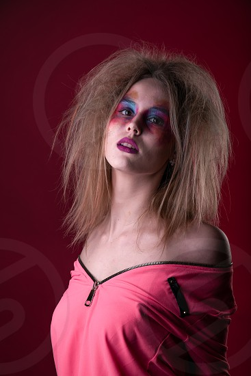Emotional Portrait of a Attractive young girl with carnival colorful makeup and disheveled hair photo