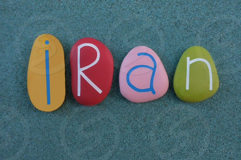 Iran Islamic Republic of Iran country in Western Asia souvenir with multi colored stone letters over green sand photo