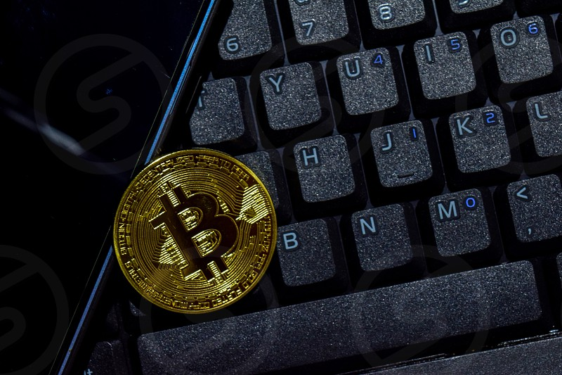 Bitcoin gold and smartphone on keyboard laptop background. Trade and business concept photo
