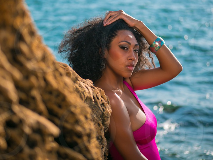 Portrait of black people pretty happy young african american woman smiling. Rocks beach. Sexy girl in pink swimsuit and jewelry enjoying nature. Travel holiday concept. photo