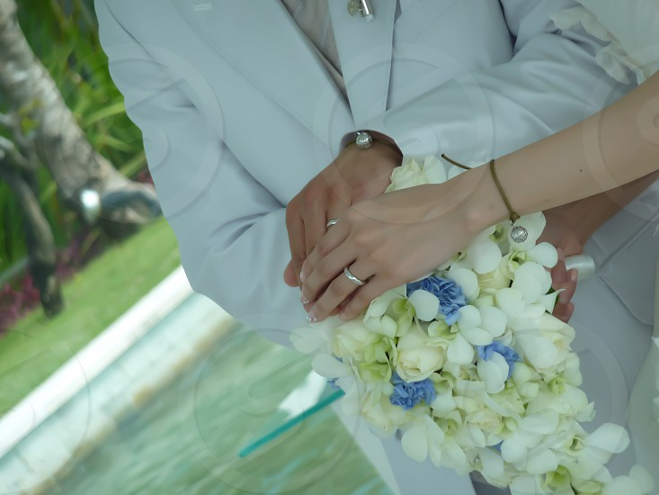 man wearing white suit holding woman's hand photo