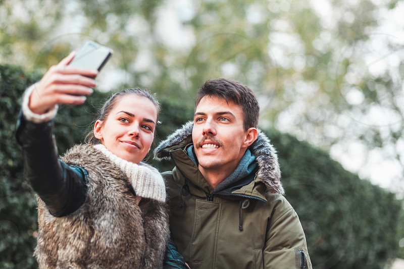 Young couple taking a selfie in a park photo