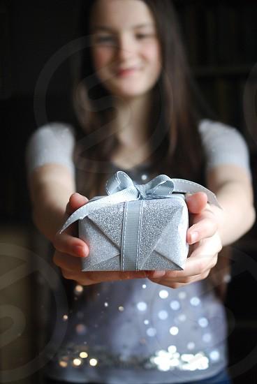 Teenage girl giving gift. photo