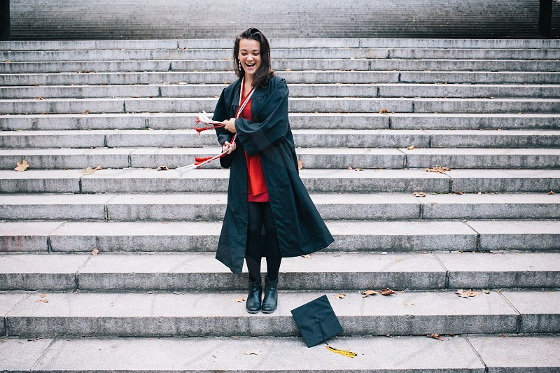 woman in graduation outfit walking and smiling photo