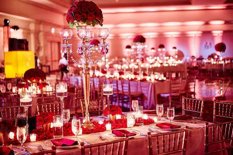 The luxury gold and red roses theme of indian wedding reception dinner table decoration with bouquet in the long vase at center surrounded with small glass vase of red roses and candle light. photo