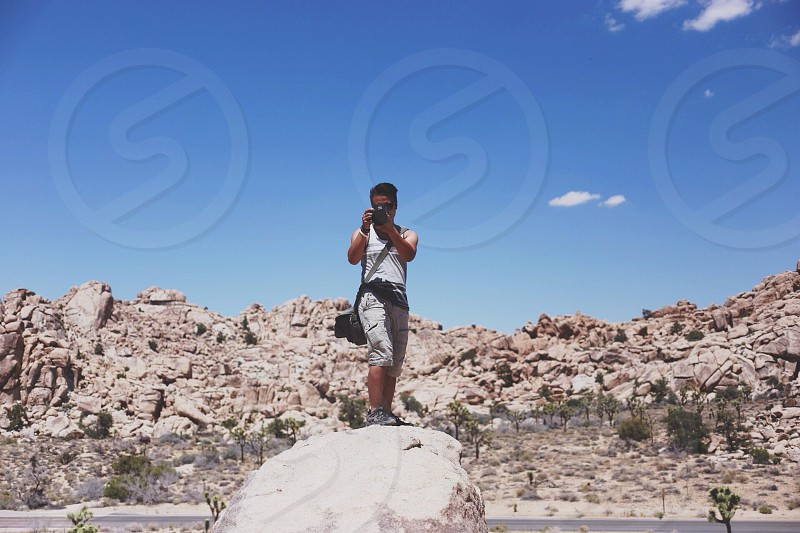 man standing on gray rock taking a picture photo