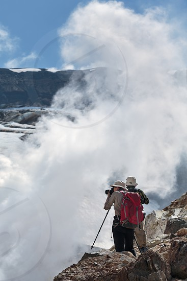 Hiking in Kamchatka: two tourists photographing and looking the smoking (steaming) fumarole on crater active Mutnovsky Volcano on a sunny day. Eurasia Far East Russia Kamchatka Peninsula. photo