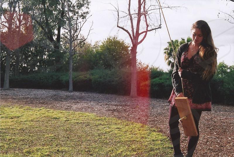 woman wearing leggings holding wooden swing photo