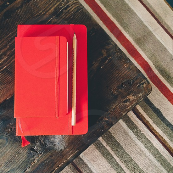 Red notebooks and pencil on corner of rustic wooden table with striped rug on floor photo