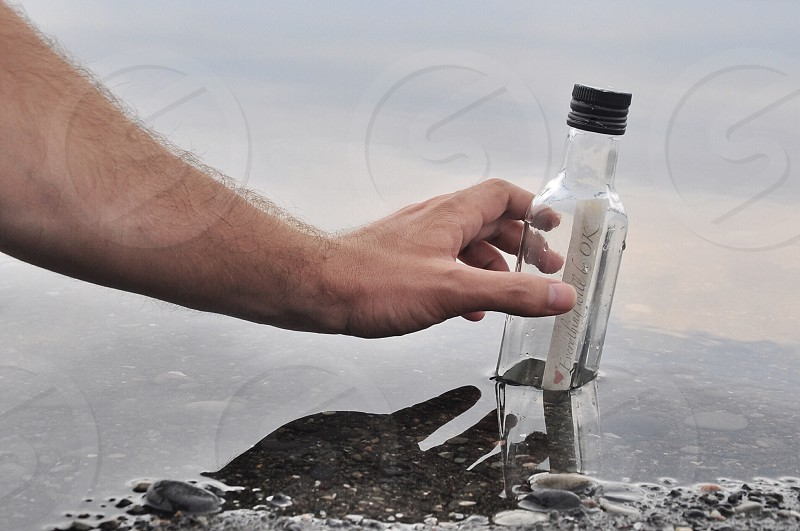 person holding bottle with message inside photo