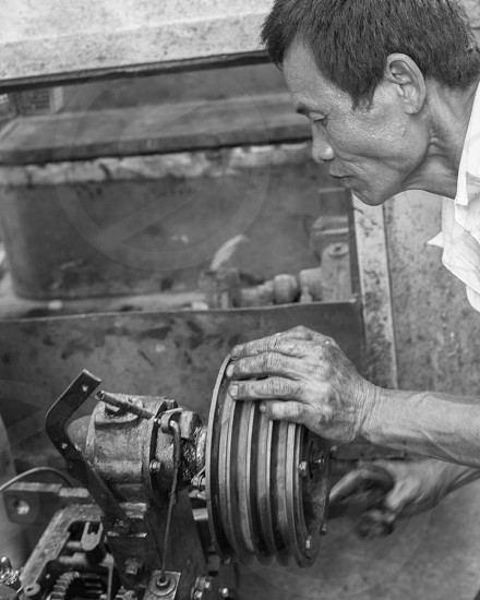 Man fixing his engine on the street. Gritty mechanical work. photo
