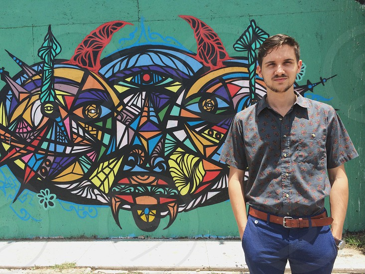 Aqua wall man floral button down shirt short sleeve button down brown leather belt colorful street art colorful street mural monster face young man with facial hair guy with hands in his pockets Houston photo