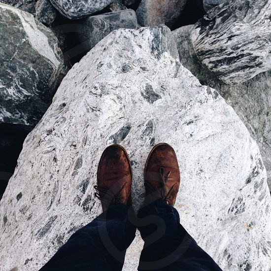 brown boots standing on a white and black rock photo