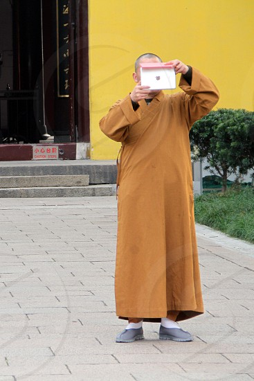 Bushist monk taking picture with 'apple' product! photo