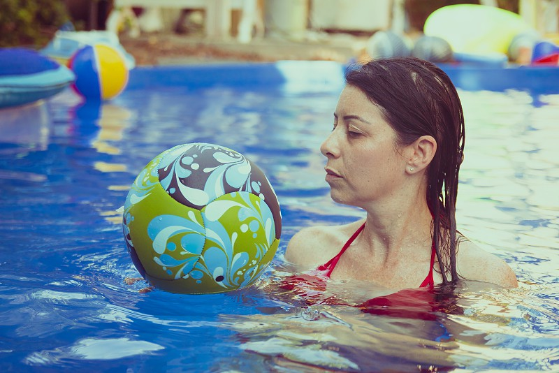 Woman play with beach ball in swimming pool. photo