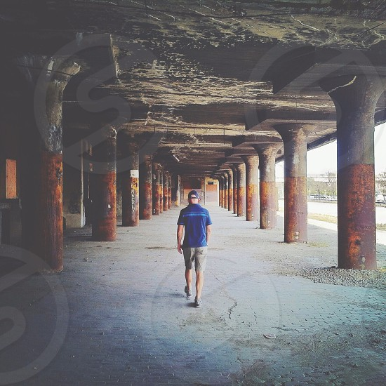 man in blue shirt walking under the concrete bridge stucture photo