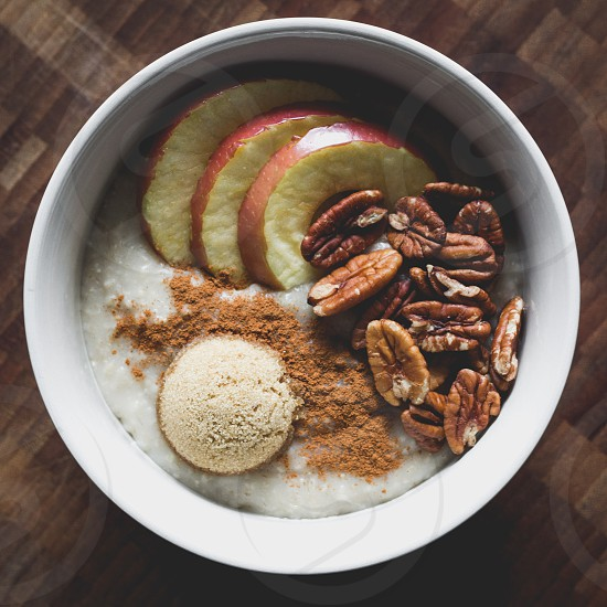 healthy bowl of oatmeal apple slices pecans cinnamon and brown sugar photo