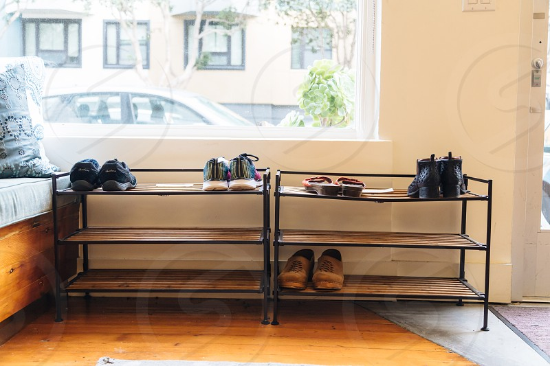 shoes align put on top of shoe rack near window beside bed during daytime photo