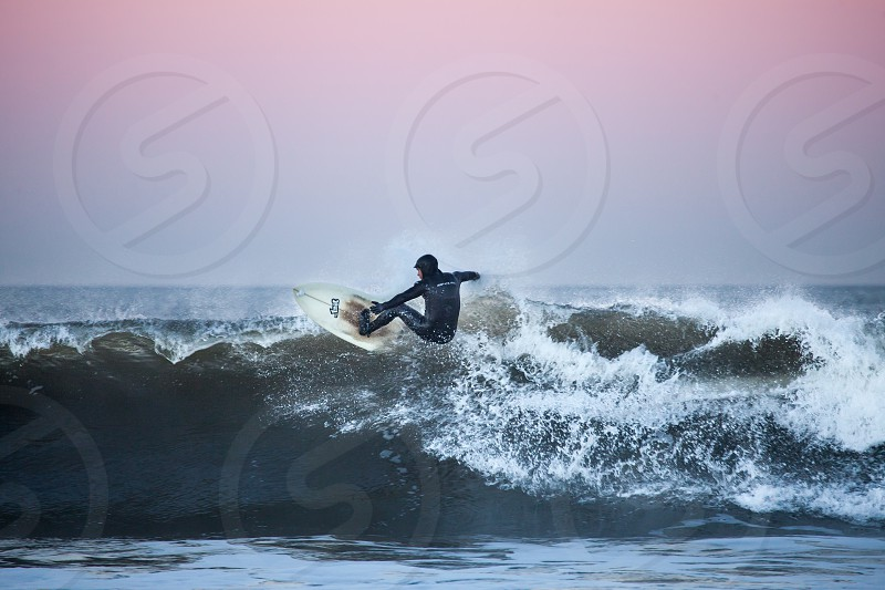 man on wet suit doing a flip on sea wave photo