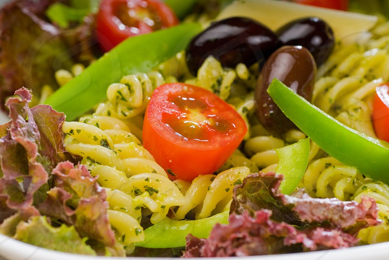 fresh healthy homemade italian fusilli pasta salad with parmesan cheesepachino cherry tomatoes black olives and mix vegetables dressed with extra-virgin olive oil and pesto sauce photo