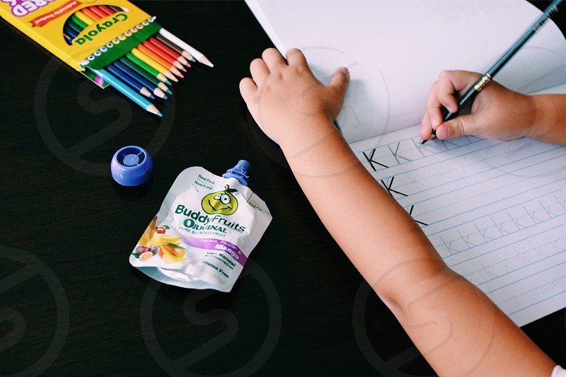 toddler holding black pen writing letter k on white lined paper beside white buddy fruits soft tube pack beside crayola color pen photo