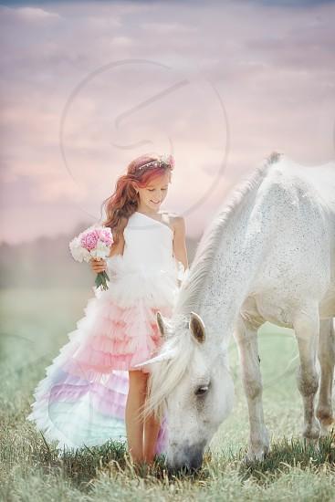 Girl with unicorn at sunrise  photo