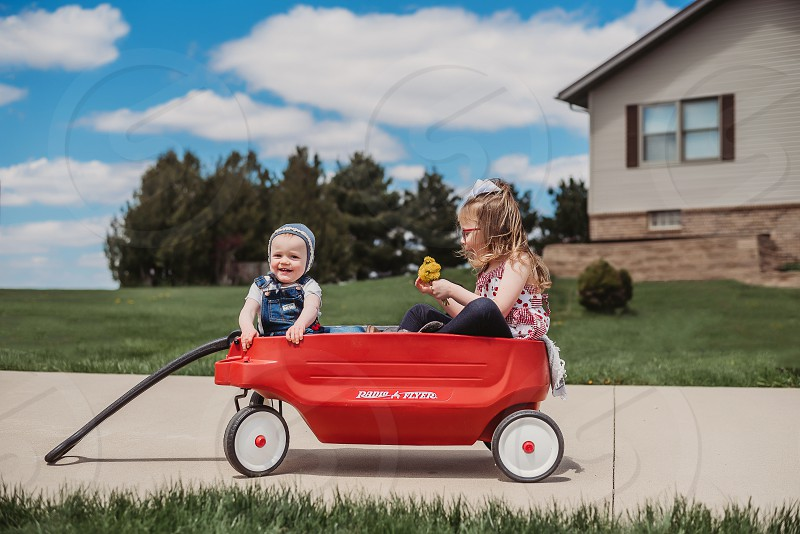 Sisters hanging outside in their little red wagon photo