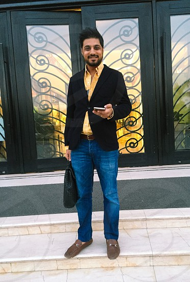 man wearing black blazer and blue denim jeans holding android smartphone while smiling photo
