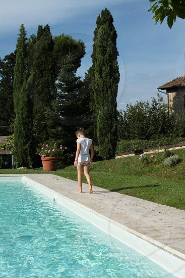 woman in white t shirt walking along the side of swimming pool during daytime photo