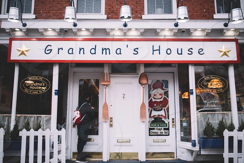 a house with brown brick wall and terrace above the white glass door with a sign posted grandma's house photo