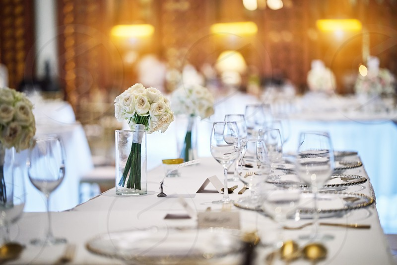 The wedding reception dinner venue setup with the white flower theme A bunch of white roses flower floral decoration on the dinner table. photo