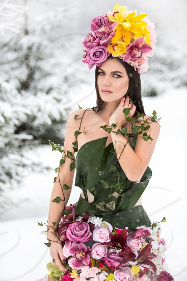 Florist girl makes her own flower dress and wears it on a cold winter day hoping it will bring spring faster. photo