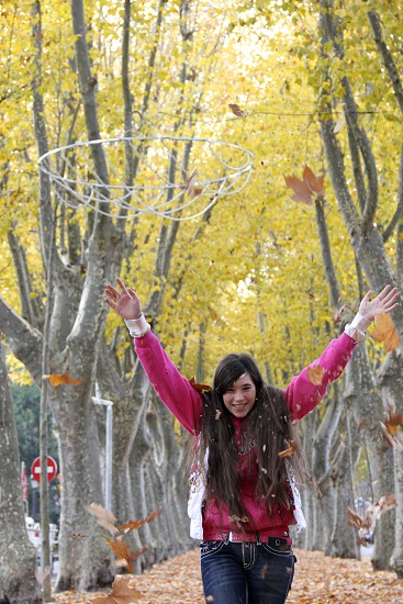 A laughing happy girl tosss yellow autumn leaves. photo