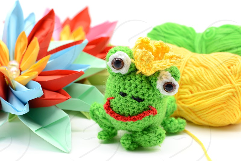 crocheted frog king with crown and paper water lily.tinker. on white isolated background photo