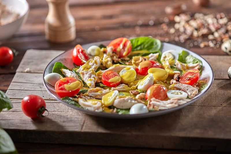Tasty appetizing homemade salad with fresh healthy ingredients - ripe vegetables chicken meat in a ceramic plate with olive sause on a wooden background. photo