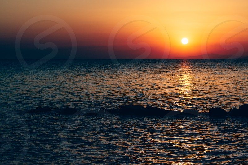 Sunset in the sea with soft wave and cloudy photo