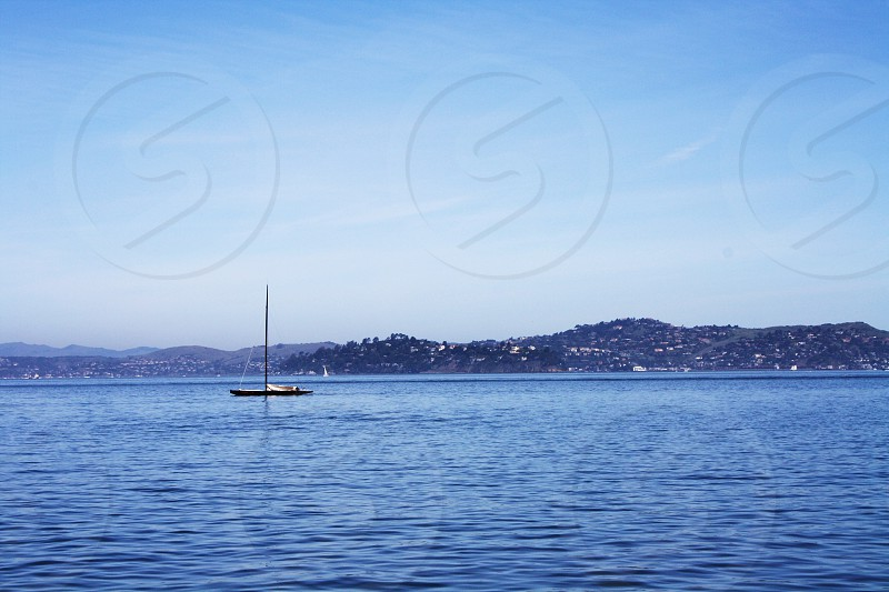 black and white boat on body of water under white and blue sky photo