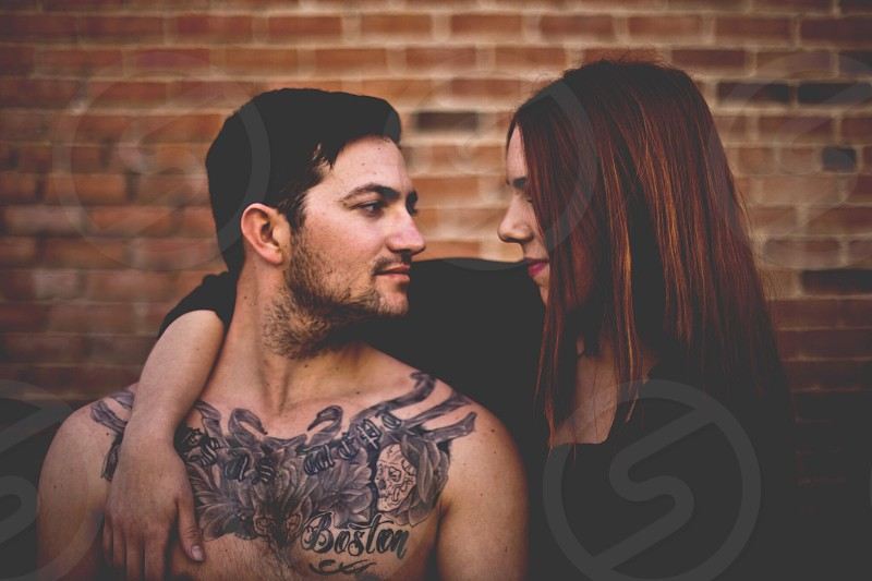 woman putting her hand over a mans shoulder looking at each other photo