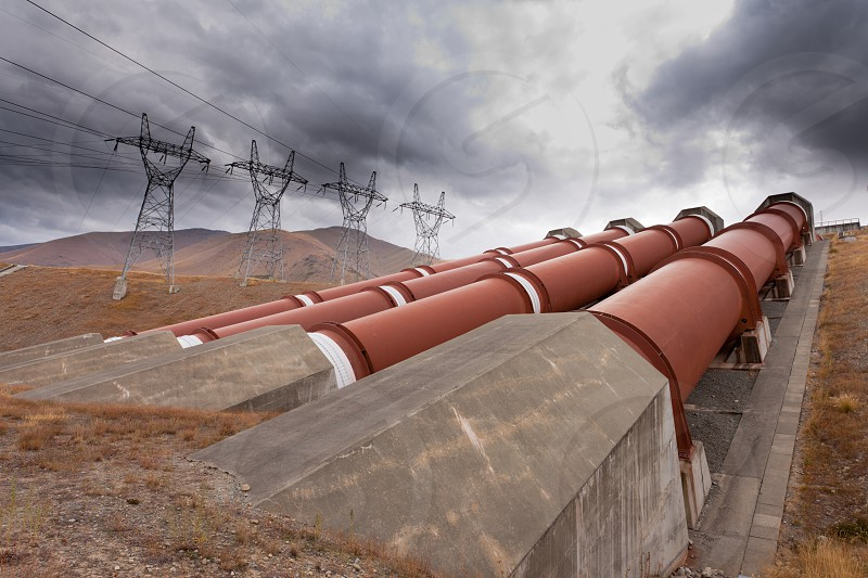 Renewable energy concept penstock water pipes in a hydroelectric power plant on barren hillside with electric trabsmission line pylons against dramatic stormy sky photo