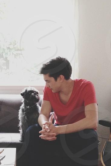 man in red round neck t-shirt sitting beside dog photo