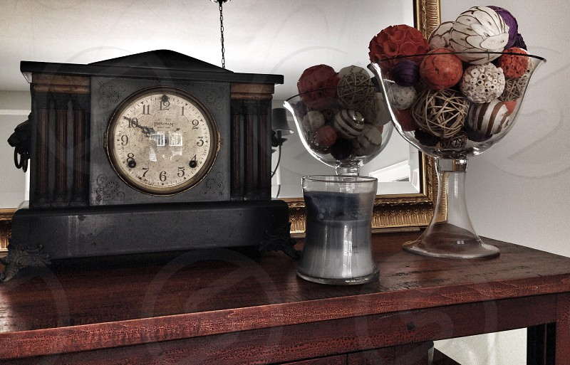 clear glass display bowl near black mantel clock photo