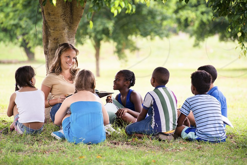 20s; 8-9; attention; black; book; boy; camp; caucasian; child; children; class; classmate; education; educator; elementary age; enjoy; female; fun; girl; girls; grass; group; happy; hispanic; job; kids; latina; learning; leisure; lesson; male; nature; outdoor; park; people; persons; pupils; reading; school; shade; sitting; student; summer; summer camp; teacher; teaching; tree; woman; working; young photo
