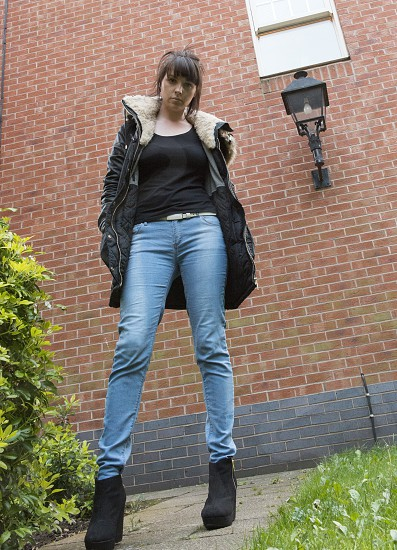woman standing wearing a black jacket and blue denim jeans with a black platform shoes photo