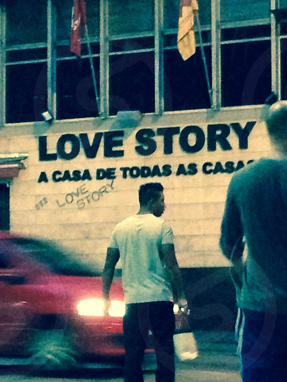 love story a casa de todos lettering on building near man in white tshirt photo